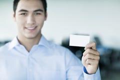 Giovane uomo d'affari sorridente che tiene un biglietto da visita ed esame della macchina fotografica Fotografie Stock