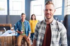 Giovane uomo d'affari sorridente con i colleghi nei precedenti Fotografie Stock Libere da Diritti