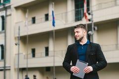 Giovane uomo d'affari sorridente con la compressa a disposizione contro lo sfondo di architettura e delle bandiere dei paesi diff Fotografia Stock Libera da Diritti
