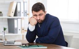 Giovane uomo d'affari stanco che si siede sul posto di lavoro in ufficio fotografia stock