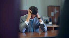 Giovane uomo d'affari stanco deludente che si siede al suo scrittorio con la sua testa che riposa sulle suoi mani ed occhi chiusi video d archivio