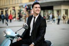 Giovane uomo d'affari sul motociclo blu fotografie stock libere da diritti
