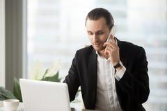 Giovane uomo d'affari in ufficio che esamina computer portatile che fa telefonata fotografia stock