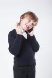 Giovane uomo d'affari in un maglione blu che parla sul telefono e sullo SMI fotografie stock