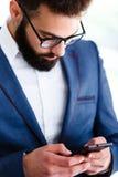 Giovane uomo d'affari Using Mobile Phone nel luogo di lavoro immagini stock libere da diritti