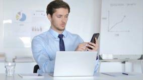 Giovane uomo d'affari Using Smartphone e computer portatile per lavoro video d archivio