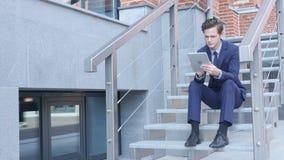 Giovane uomo d'affari Using Tablet, passare in rassegna, sedentesi sulle scale fuori dell'ufficio archivi video