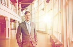 Giovane uomo d'affari in vestito al corridoio dell'edificio per uffici Immagini Stock
