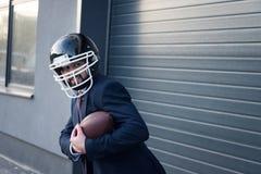 giovane uomo d'affari in vestito e casco di rugby con la palla nello stare delle mani fotografie stock