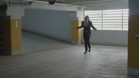 Giovane uomo d'affari in vestito e legame che va nel parcheggio sotterraneo che guarda intorno e che comincia ballare divertente  stock footage