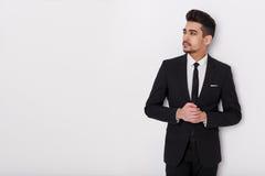 Giovane uomo d'affari in vestito nero su un fondo bianco Uomo sicuro che guarda a partire dalla macchina fotografica fotografia stock libera da diritti