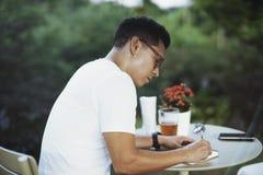 Giovane uomo dagli occhiali che beve birra fredda e che scrive alcune note in taccuino fotografia stock