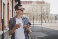 Giovane uomo dei pantaloni a vita bassa che cammina sulla via e che per mezzo del suo smartphone Immagine Stock