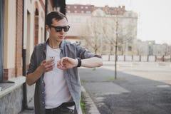 Giovane uomo dei pantaloni a vita bassa che cammina sulla via, esaminante orologio e per mezzo del suo smartphone Con lo spazio d Immagine Stock