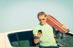 Giovane uomo dei pantaloni a vita bassa con musica d'ascolto dello smartphone durante il viaggio Immagine Stock