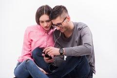 Giovane uomo dei pantaloni a vita bassa in vetri e donna che si siedono e sguardo al telefono Fotografie Stock Libere da Diritti