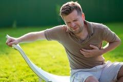 Giovane uomo del caucasain che ha attacco di cuore mentre sedersi all'aperto fotografia stock libera da diritti