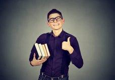 Giovane uomo del nerd in vetri con il libro che mostra pollice su Immagine Stock Libera da Diritti