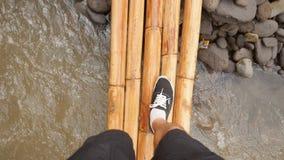Giovane uomo del viaggiatore che cammina sul piccolo ponte di bambù sopra il fiume della giungla nel punto di vista tropicale del archivi video