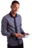 Giovane uomo dell'afroamericano che per mezzo di un pc del ridurre in pani Fotografia Stock
