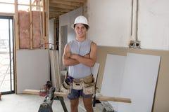 Giovane uomo dell'apprendista di industria del costruttore sul suo 20s che indossa casco protettivo che impara lavoro al sito ind Fotografia Stock Libera da Diritti