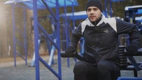 Giovane uomo dell'atleta che fa esercizio alla palestra all'aperto nel parco di inverno Immagini Stock