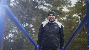 Giovane uomo dell'atleta che fa esercizio di spinta-UPS sulle barre nel parco di inverno all'aperto Fotografie Stock Libere da Diritti