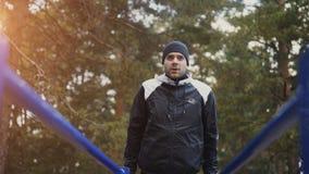 Giovane uomo dell'atleta che fa esercizio di spinta-UPS sulle barre nel parco di inverno all'aperto Fotografie Stock