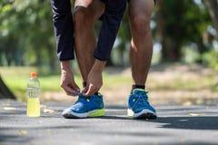Giovane uomo dell'atleta che lega le scarpe da corsa nel parco all'aperto, corridore maschio pronto per pareggiare sulla strada f fotografia stock