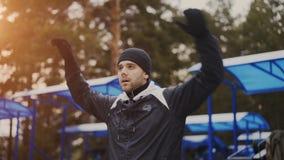 Giovane uomo dell'atleta che si scalda prima dell'addestramento di allenamento nel parco di inverno Immagini Stock Libere da Diritti