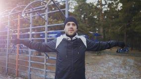 Giovane uomo dell'atleta che si scalda prima dell'addestramento di allenamento nel parco di inverno Immagine Stock Libera da Diritti