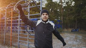 Giovane uomo dell'atleta che si scalda prima dell'addestramento di allenamento nel parco di inverno Fotografia Stock