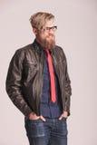 Giovane uomo della barba che sorride con entrambe le mani in sua tasca Immagini Stock Libere da Diritti