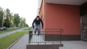 Giovane uomo della via che fa esercizio del parkour con le scale archivi video