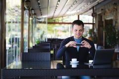 Giovane uomo dello studente che prende foto di una tazza di caffè e che utilizza computer portatile nella mensa al caffè della vi Fotografia Stock Libera da Diritti
