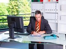 Giovane uomo di affari alla sua scrittura dello scrittorio Immagini Stock