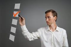 Giovane uomo di affari in camicia bianca che verifica la scatola della lista di controllo Fondo grigio Fotografie Stock Libere da Diritti