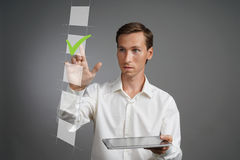 Giovane uomo di affari in camicia bianca con il computer della compressa che verifica la scatola della lista di controllo Fondo g Fotografia Stock Libera da Diritti