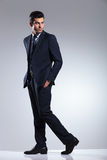 Giovane uomo di affari che cammina sul fondo grigio dello studio Immagini Stock