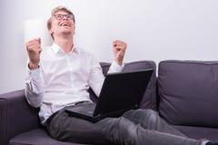 Giovane uomo di affari che incoraggia il suo successo mentre lavorando al computer portatile Immagine Stock Libera da Diritti