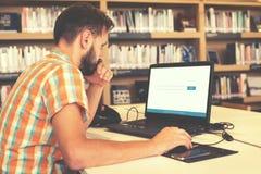 Giovane uomo di affari che lavora al suo computer portatile Fotografie Stock Libere da Diritti