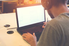 Giovane uomo di affari che lavora al suo computer portatile Immagini Stock Libere da Diritti