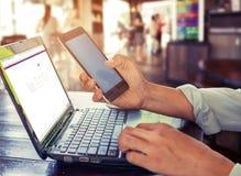 giovane uomo di affari che lavora al suo computer portatile e che utilizza Smart Phone che si siede alla tavola di legno in una c Immagine Stock Libera da Diritti