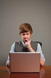 Giovane uomo di affari che pensa con il computer portatile Immagini Stock Libere da Diritti