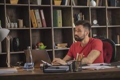 Giovane uomo di affari che pensa mentre lavorando con il taccuino su che progetto seguente Fotografia Stock Libera da Diritti