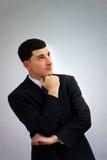 Giovane uomo di affari che pensa nel vestito nero immagine stock