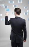 Giovane uomo di affari che preme un tasto dello schermo attivabile al tatto Fotografia Stock