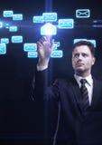 Giovane uomo di affari che preme uno schermo attivabile al tatto della busta Fotografia Stock