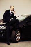 Giovane uomo di affari che rivolge al telefono Immagine Stock