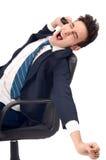 Giovane uomo di affari che sbadiglia nella sedia esecutiva. Immagine Stock